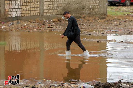شاب يعبر مياه الامطار المتراكمه