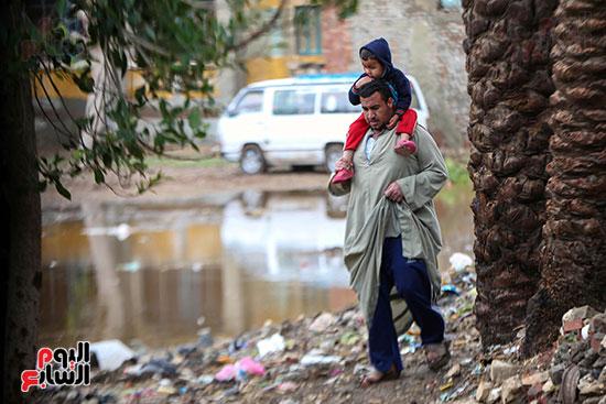 رجل يحمل طفله لتعثر تحركه فى شاره متاثر بالامطار