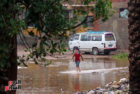 طفل يعبر مياه الامطار