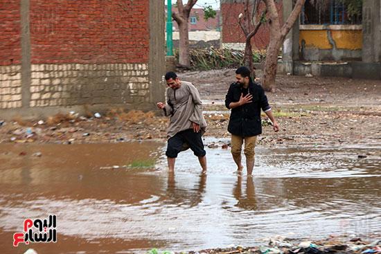 شباب يعبرون مياه الامطار بالشارع