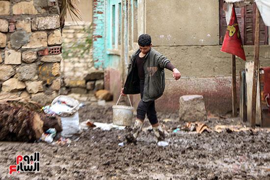 شاب يزيل مياه الامطار