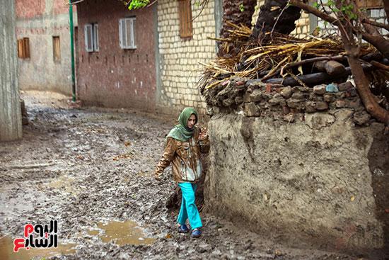 طفلة تمر من شارع تاثر بالامطار