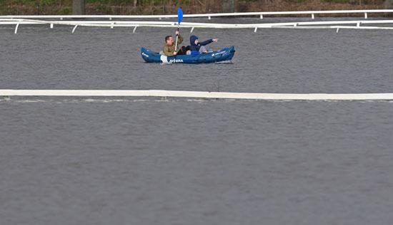 شخصان يسيران بمركب وسط مياه الامطار