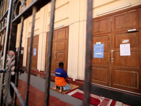 مسلم يؤدى الصلاة خارج المسجد المغلق بالبحرين