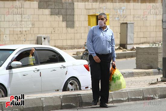 ارتداء مواطن كمامه للحمايه من الفيروس والاتربه (2)