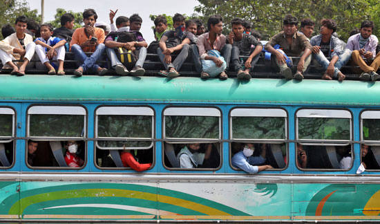 يسافر-الناس-في-حافلة-مزدحمة-للعودة-إلى-مدنهم-وقراهم-قبل-بدء-الإغلاق
