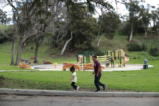 يسير-الناس-بالقرب-من-ملعب-مغلق-بعد-أن-أصدرت-كاليفورنيا-أمرًا-بالبقاء-في-المنزل