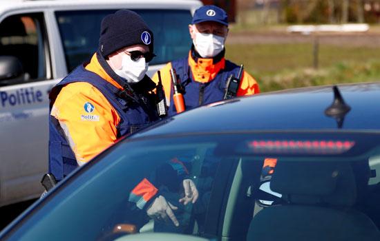 ضباط-شرطة-بلجيكيون-يرتدون-قناعًا-وقائيًا-على-الحدود-البلجيكية-الهولندية-أثناء-الإغلاق-الذى-فرضته-الحكومة-البلجيكية--(2)