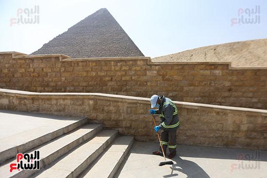عامل يقوم بالتنظيف فى منطقه اهرامات الجيزه