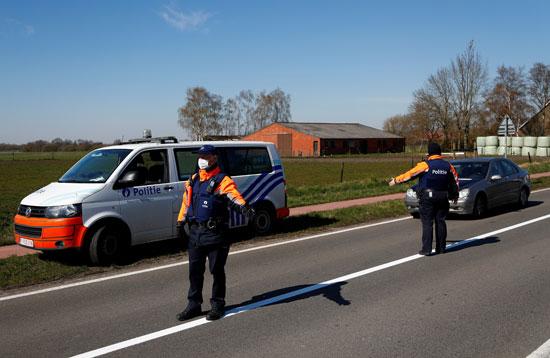 ضباط-شرطة-بلجيكيون-يرتدون-قناعًا-وقائيًا-على-الحدود-البلجيكية-الهولندية-أثناء-الإغلاق-الذى-فرضته-الحكومة-البلجيكية--(1)