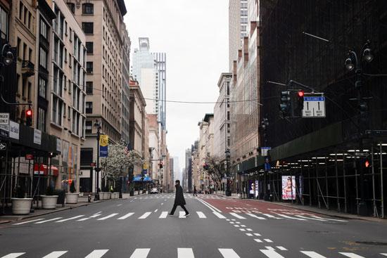 رجل-يعبر-شارعًا-خامسًا-تقريبًا-فارغًا-في-وسط-مدينة-مانهاتن-في-نيويورك