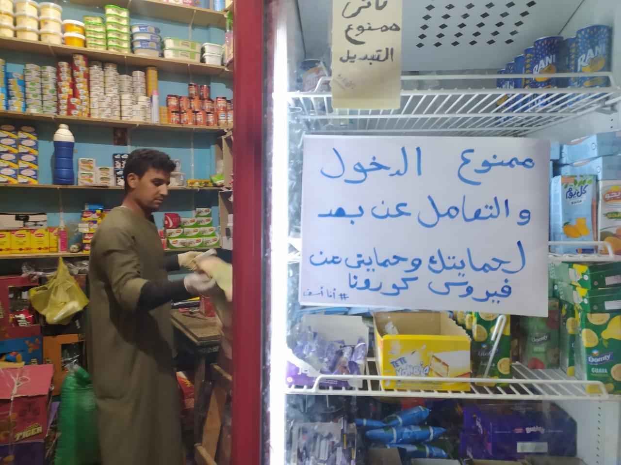 لافتة بمحل بقالة لمنع العدوى بكورونا