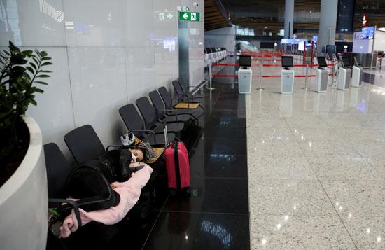 فتاة تنام داخل المطار بسبب وقف رحلات الطيران