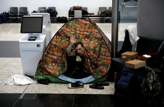 روسى يجلس داخل خيمته بمطار اسطنبول