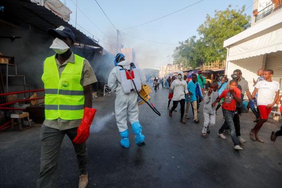 أحد أفراد خدمات النظافة المحلية أثناء تعقيمه في الشارع والسوق بداكار