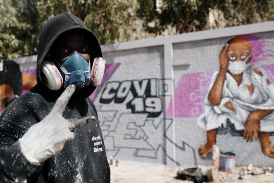 رد فعل لفنان جرافيتي وهو يقف بجانب جداريته