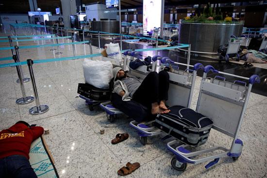 رجل ينام على عربة الحقائب بمطار اسطنبول