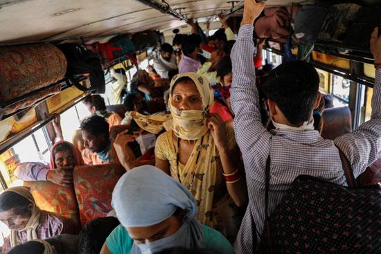 عمال مهاجرون في حافلة ولاية أوتار براديش لنقل خلال فترة إغلاق استمرت 21-يومًا بالهند