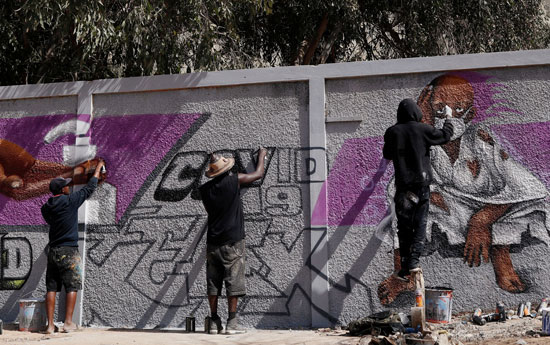 فنانو الجرافيتى يعمل على جدارياتهم لتشجيع الناس على حماية أنفسهم من فيروس كورونا