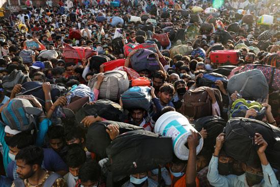 العمال المهاجرون يتجمعون خارج محطة للحافلات وينتظرون ركوب الحافلات للعودة إلى قراهم