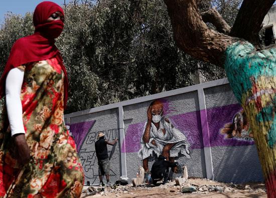 امرأة تمشي أمام فناني جرافيتى وهم يعملون على جدارياتهم لتشجيع الناس على حماية أنفسهم