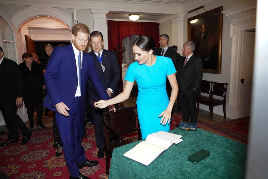 ميجان ماركل تمرر القلم إلى هارى لتسجيل اسمه