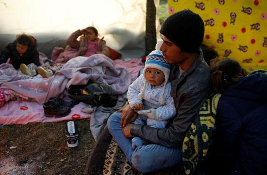 مهاجرون يستريحون بالقرب من معبر بازاركولي الحدودي التركى