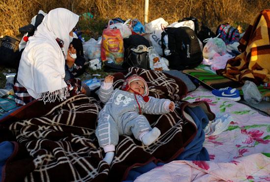 مهاجرون يستريحون بالقرب من معبر بازاركولي الحدودي التركية