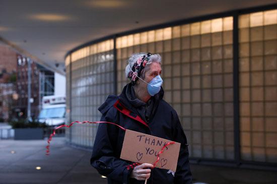 مواطن يحمل لافتة شكر للطواقم الطبية فى نيويورك على مجهودهم فى مكافحة كورونا