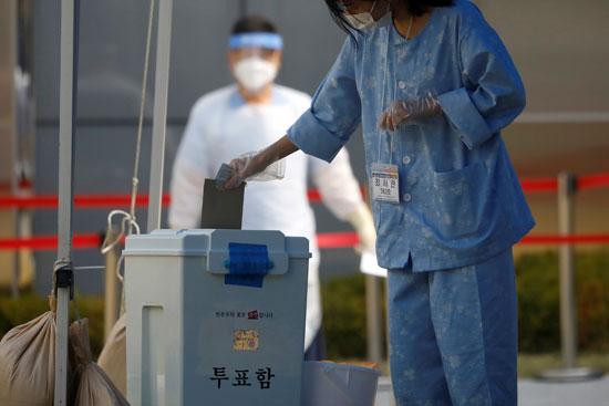 مصابة بكورونا تضع بطاقة التصويت فى صندوق الاقتراع