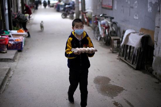 طفل يحمل بيضًا فى منطقة سكنية فى ووهان