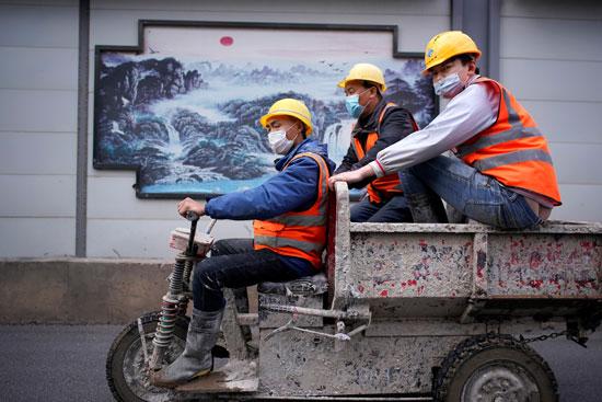 عمال يرتدون أقنعة وجه