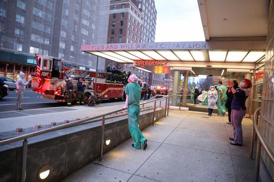 أمريكيون يشاركون رجال الإطفاء فى توجيه التحية للطواقم الطبية بنيويورك