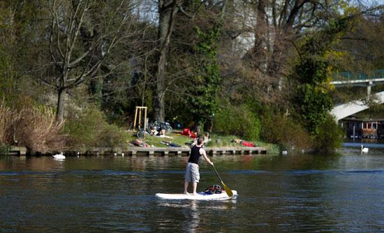رجل-يركب-على-لوح--على-نهر-سبري-أمام-جزيرة-الشباب-في-يواكيم-هيرمان-ببرلين