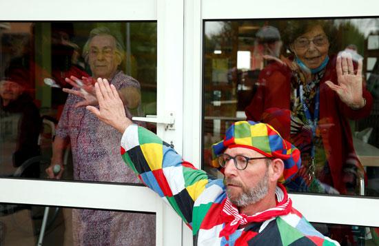 رجل-يرتدي-زي-مهرج-فى-كرنفال-محلى-ومسنات-يلوحن-فى-دار-رعاية-دي-كاسل-فى-فرنسا