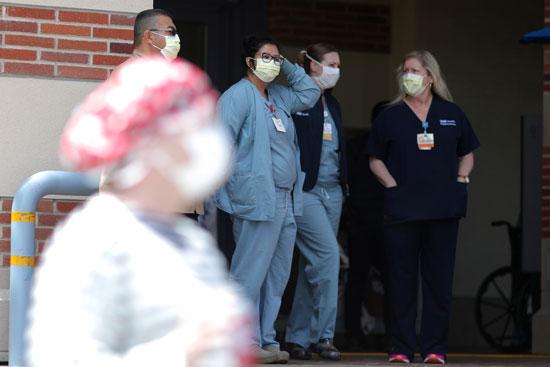 الممرضات يقفن في مدخل المستشفى يراقبن احتجاج الممرضات على معدات الوقاية الشخصية في المركز الطبي بجامعة كاليفورنيا في لوس أنجلوس
