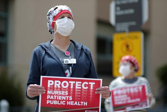 العاملون بالرعاية الصحية يرفعون لافتات أثناء احتجاجهم