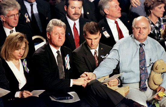الرئيس الأمريكي الأسبق  بيل كلينتون يمسك بيد زوج إحدى المفقودات فى الحادث خلال صلاة لتكريم ضحايا التفجير