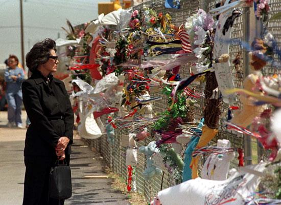 سيدة تقف أمام النصب التذكارى للضحايا