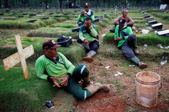 حفارو القبور وهم ينتظرون توابيت جديدة بإندونيسيا