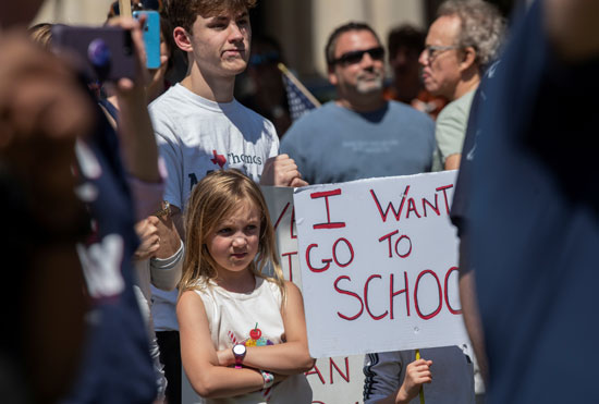 طفلة تقف بجوار لافتة أريد العودة للمدرسة