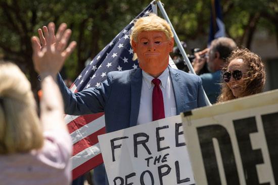 دمية تشبة ترامب تحمل لافتة عودة الحرية