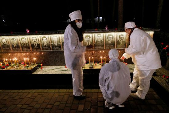 مشاركون يرتدون الكمامات أثناء إحياء ذكرى الضحايا