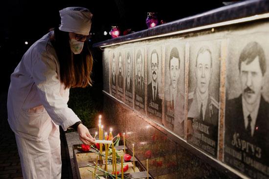 سيدة تضىء الشموع لإحياء ذكرى الضحايا