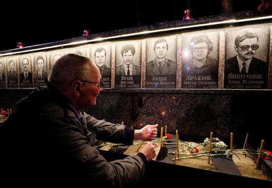 عجوز ينظر لصور الضحايا فى النصب التذكارى