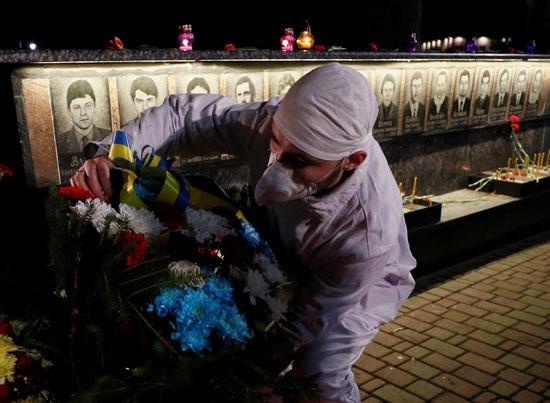 رجل يضع ورود على النصب التذكارى لضحايا تشرنوبل