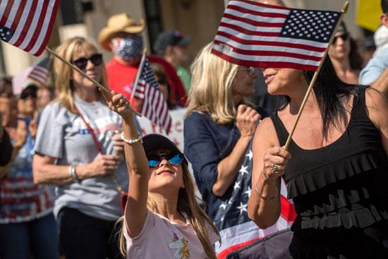 طفله ترفع علم أمريكا خلال الوقفة