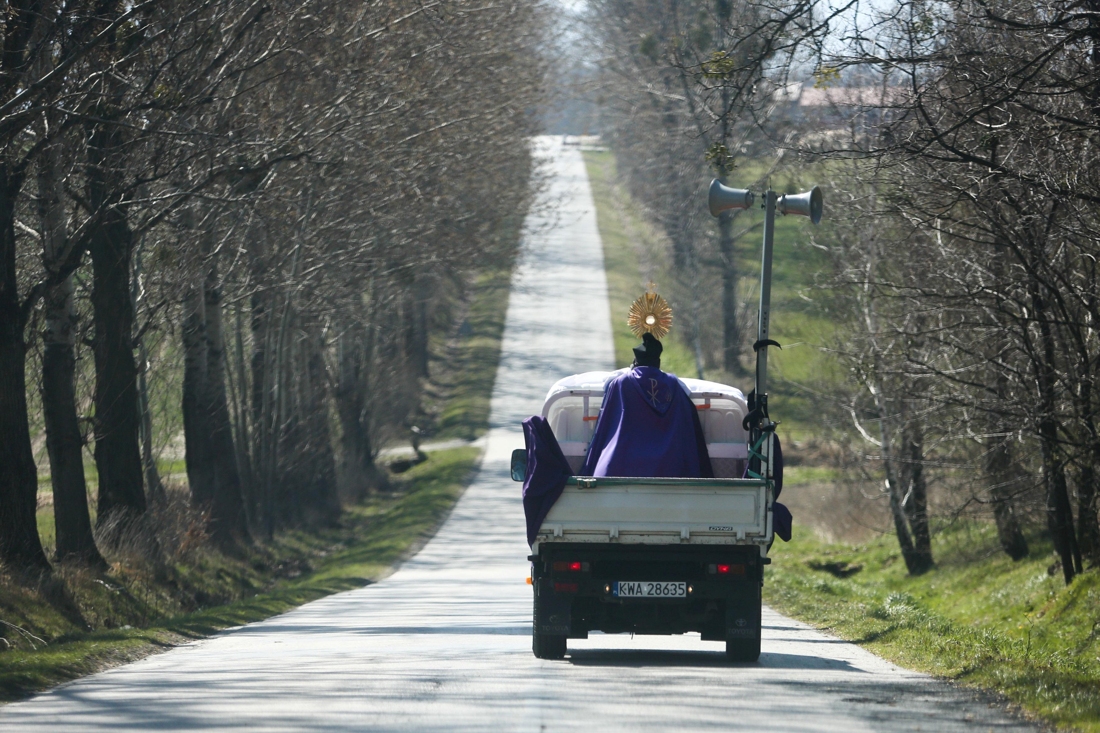 كاهن يرتدي قناعًا وقائيًا يقف على شاحنة صغيرة ويبارك المسيحيين فى القرى خلال أحد الشعانين في نيديك ببولندا