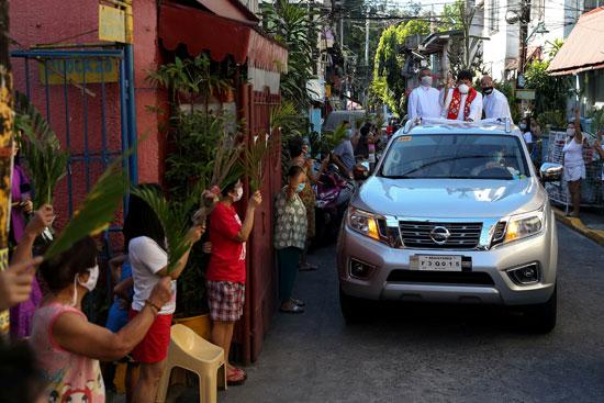 كاهن يتجول بسيارته فى الشوارع الفلبينيه ليبارك المحتفلين أمام منازلهم