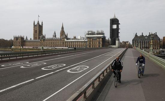 راكبو الدراجات فوق جسر ويستمنستر الفارغ تقريبًا من حركة المارة